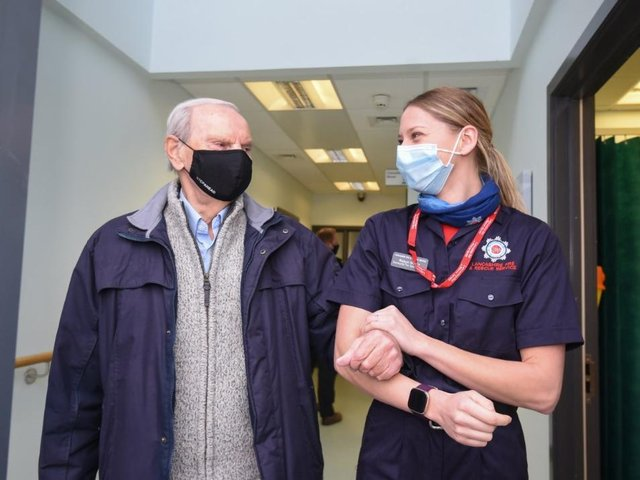 Geoffrey Mitchell is walked out of Lytham Primary Care Centre by Lancashire Fire and Rescue Service community safety officer Robyn Morris after having a Covid-19 vaccine on Wednesday, January 13, 2021 (Picture: Daniel Martino for JPIMedia)