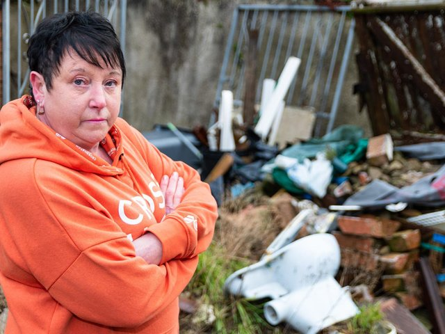 Jeanette Hyde outside the rear of 95 Saville Road in Blackpool, which the rubbish that has been dumped in the back yard. Photo: Kelvin Stuttard