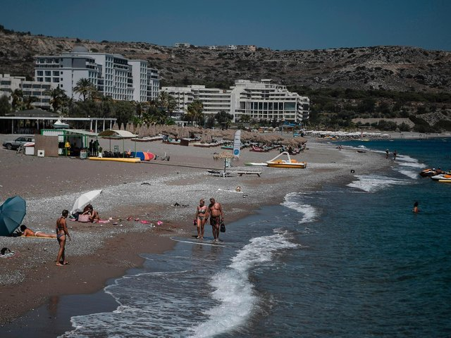 Tourists walk the beach in front of hotels on the Aegean island of Rhodes