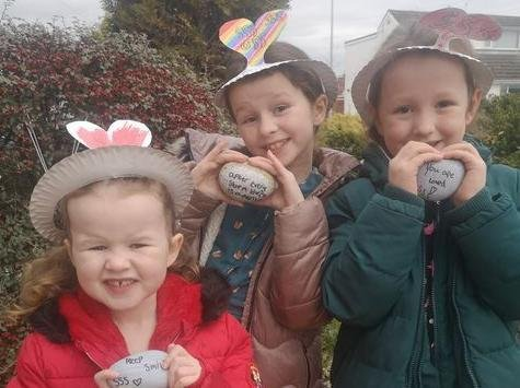The Mawdsley sisters, Mollie, four, Delilah, eight (middle) and Eva Jean, seven, have been leaving rocks with rainbows and positive messages on their neighbours' doorsteps. Photo: Karen Feather