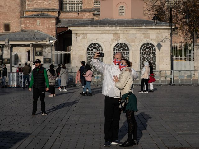 Tourists take a selfie in front of the Hagia Sophia Grand Mosque during a national weekend coronavirus lockdown on December 06, 2020, in Istanbul, Turkey