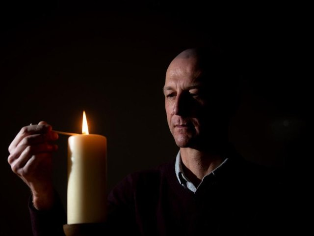 Dr Jason Cupitt, who is in charge of Blackpool Victoria Hospital's Covid intensive care unit, lights a candle in the hospital's chapel to remember the pandemic's victims (Picture: Dan Martino for JPIMedia)