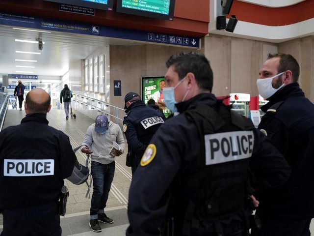 French policemen control the travel certificates of a passenger arriving at the Mulhouse main train station