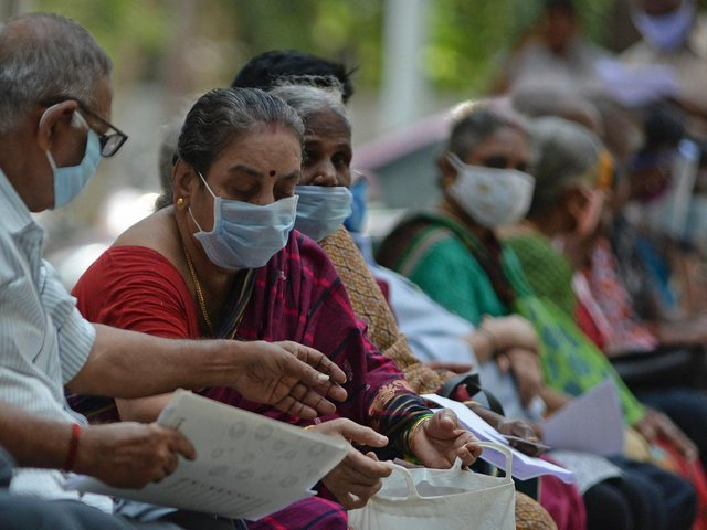 People wait for their turn to receive the Covid-19 coronavirus vaccine at a government hospital in Chennai  (Photo by ARUN SANKAR/AFP via Getty Images)