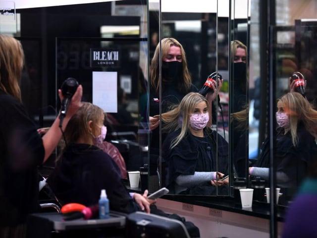 A customer has her hair dried following a haircut inside a hairdresser's salon in London