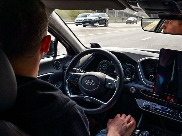 A picture taken on April 15, 2021 shows engineer Alexey keeping his hands on his knees as the self-driving car, developed by Russian internet giant Yandex, moves along a road in Moscow