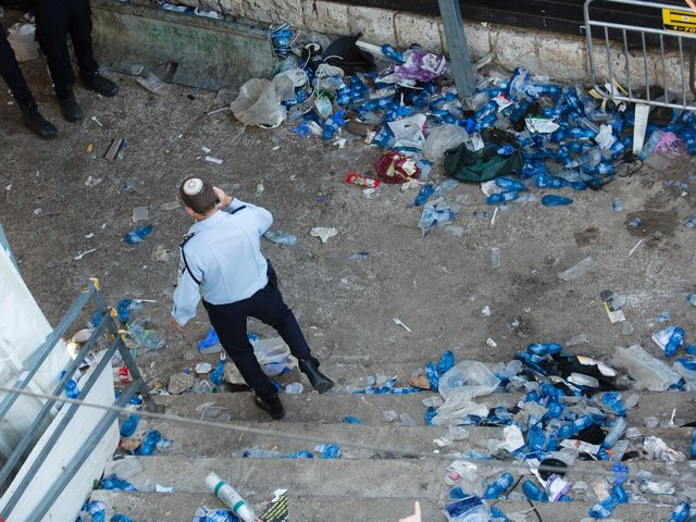 A police officer walks at the scene where dozens were killed in a crush at a religious festival in Mount Meron on April 30, 2021 in Meron, Israel. At least 44 people were crushed to death and over 150 more injured in a stampede, as tens of thousands of ultra-Orthodox Jews gathered to celebrate the Lag B'omer event, late Thursday. (Photo by Amir Levy/Getty Images)