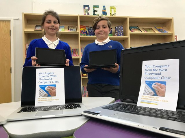 Head girl Sophia Cox and head boy Matthew Foley at Poulton St Chad's Primary School with some of the newly refurbished laptops