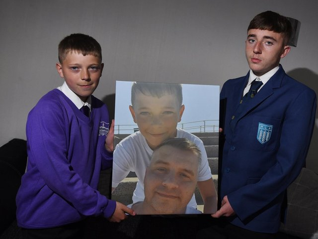 Kai Ryder, 11, with older brother Haydyn, holds his favourite photograph of him and his dad, Rob Ryder, who died of cancer.