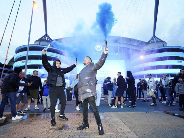 Fans celebrate outside Etihad Stadium as Manchester City are crowned champions