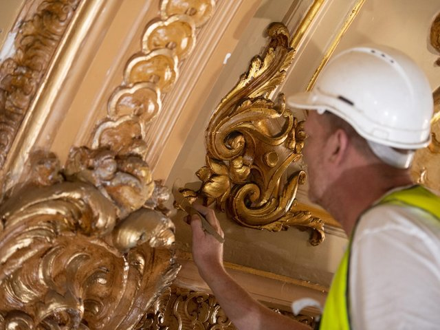 A craftsmen gives the ballroom ceiling a fresh look