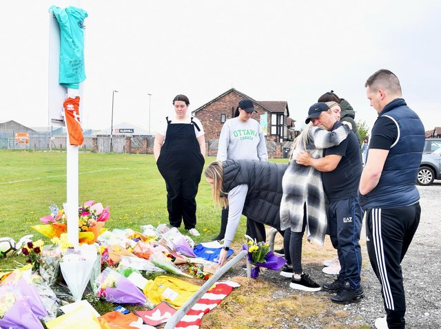 People lay flowers and cards at Common Edge playing fields today