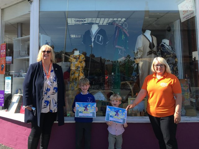 Teddy and Barnaby Couch receiving their certificates from Home-Start chief executive Pat Naylor (left) and shop manager Sue Uttley.