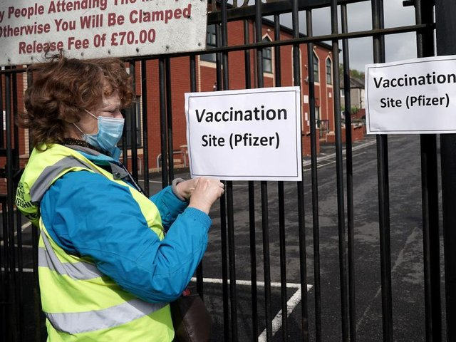 A volunteer gives puts up signs outside a mobile vaccination clinic set up at the Masjid E Sajedeen Mosque in Little Harwood on May 24, 2021 in Blackburn