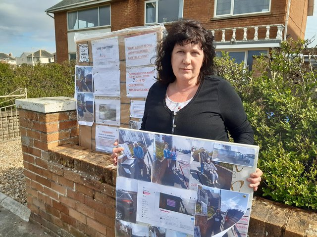 Paula Storton with the sign outside her home