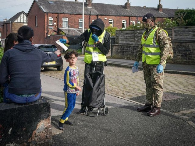 Children play in the street as gunners from the Royal Horse Artillery distribute Covid-19 polymerase chain reaction (PCR) tests to local residents in Bolton