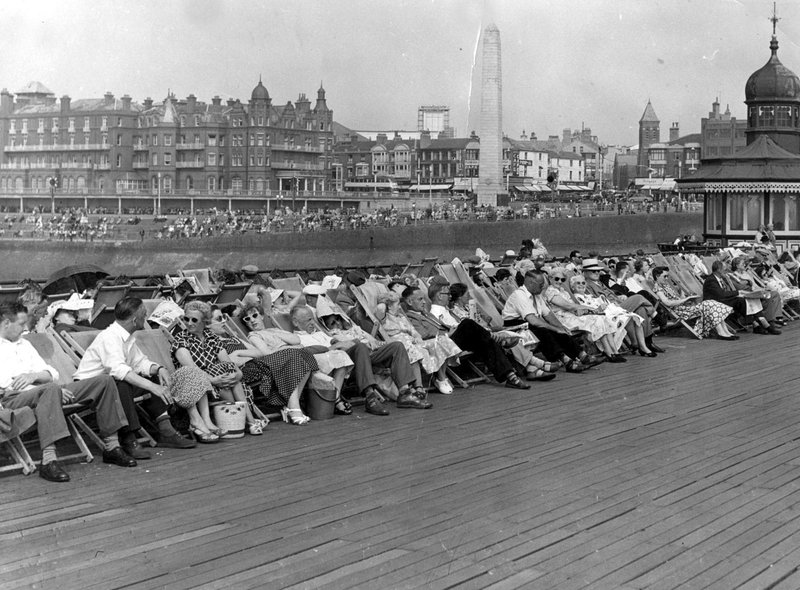 Holidaymakers relaxing in deckchairs on North Pier in 1955