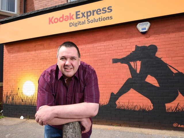 John Ormston has opened Kodak Express and Cable Express on Highfield Road. Here with the mural done by Blackpool street artist Seca One