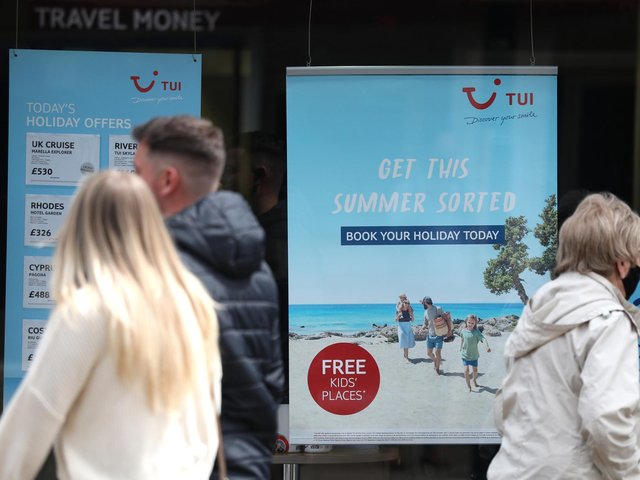 People make their way past the shop window of a Tui store