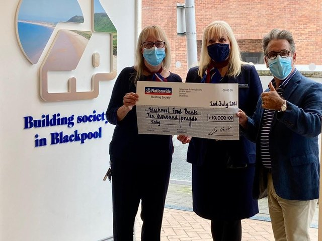 Neil Reid of Blackpool Food Bank receives the cheque from Nationwide representatives