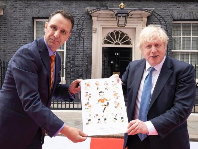 Chris Hull presents the Morty celebration artwork to Prime Minister Boris Johnson outside No 10 Downing Street.