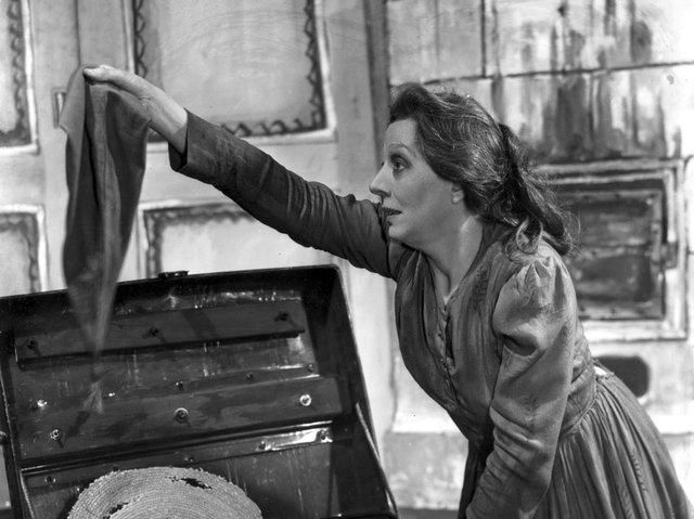 Dame Edith Evans searches through an old tin trunk in a scene from 'Crime and Punishment' at the New Theatre, 1946. Pic: Getty Images