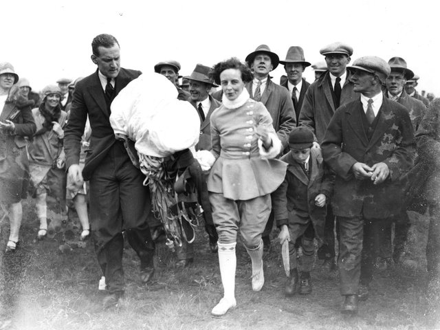 A crowd following Miss June after she had completed a parachute jump from an air balloon at Blackpool Air Pageant.  (Photo by Central Press/Getty Images)